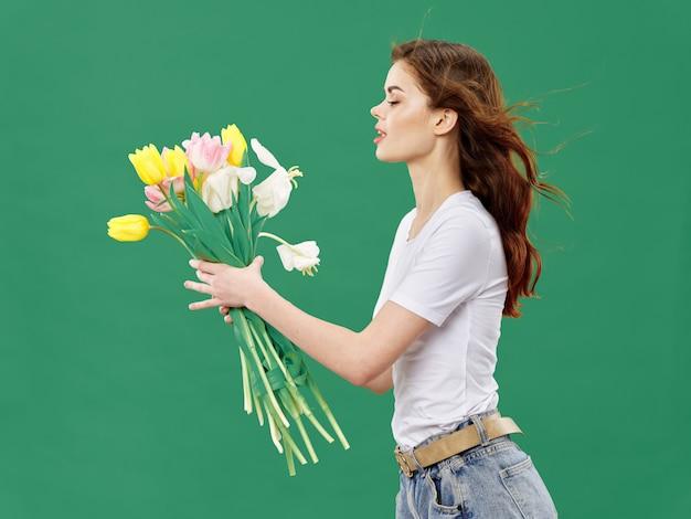 Primavera hermosa joven con flores en un estudio de color. mujer posando con un ramo de flores.