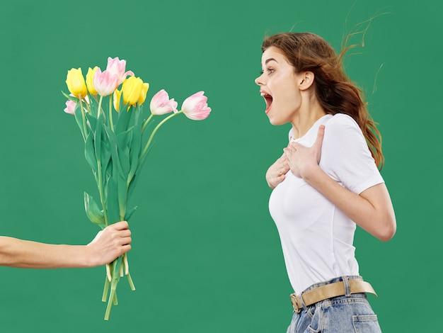 Primavera joven hermosa niña con flores sobre un fondo de estudio de color, mujer posando con un ramo de flores, día de la mujer