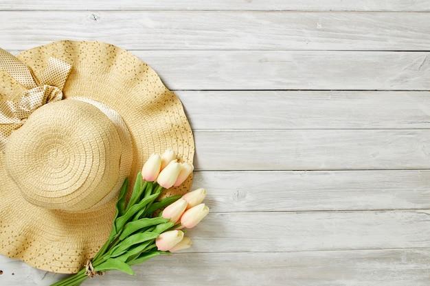 Primavera o verano con tulipanes y sombrero.