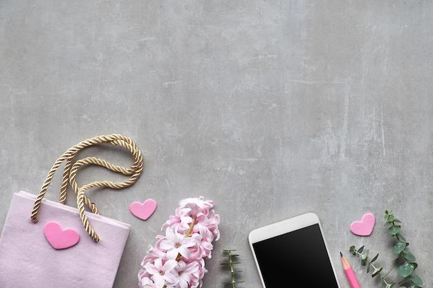 Primavera plana con flor de jacinto de perlas, eucalipto, teléfono móvil y bolsa de figt en piedra, espacio de texto