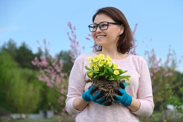 Primavera retrato de mujer de mediana edad en guantes con flores de prímula amarilla en manos en el jardín