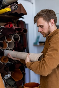 Primer artesano masculino teniendo paquete de material para trabajar en el taller de cuero haciendo artesanía en cuero