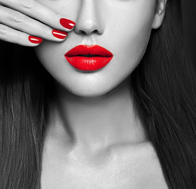 Primer atractivo rosado de los labios y de las uñas. boca abierta. manicure y maquillaje.