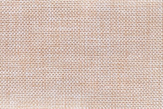 Primer beige del fondo de la materia textil. estructura de la macro de la tela.