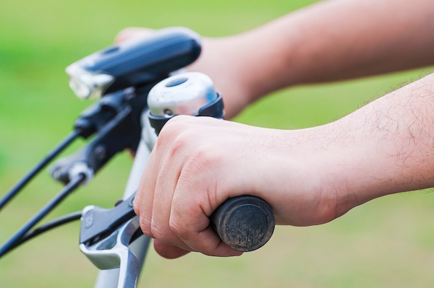 Primer de la bicicleta del montar a caballo de la mano del muchacho. la foto está enfocada en la mano más cercana.