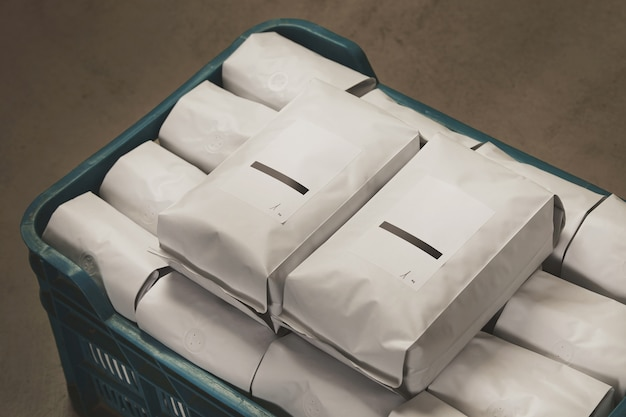 Primer blanco lleno de paquetes sellados de café o té en una caja de plástico sobre un piso de concreto en el almacén.