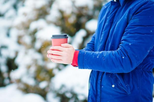 Primer café para ir en manos masculinas en el día de invierno congelado al aire libre
