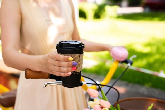 Primer café sostenido por una mujer elegante