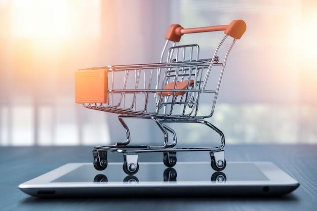 Primer del carro de compras en el estacionamiento en la tableta. compras en línea y trabajo desde el concepto de hogar.