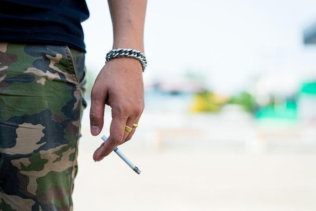 Primer cigarrillo en la mano del hombre joven con humo