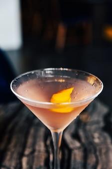 Primer cóctel rosado lleno de rodajas de cáscara de yuzu en copa de vino en la mesa de mármol.