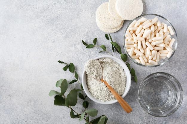 Primer colágeno para preparar una máscara cosmética en un tazón de cerámica con cuchara y cápsulas para alimentos dietéticos, esponjas de lufa y ramas secas de eucalipto en la vieja mesa de hormigón gris. endecha plana