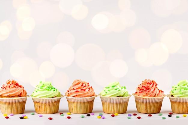 Primer colorido sabroso de las magdalenas en fondo del bokeh con el espacio de la copia. dulces de fiesta de cumpleaños