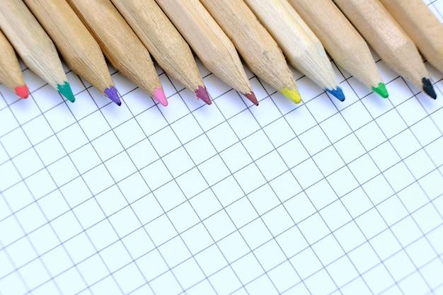 Primer conjunto de lápices multicolores en la hoja de papel a cuadros del cuaderno para el dibujo. concepto de regreso a la escuela.