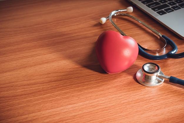 Primer del corazón y del estetoscopio en el escritorio. concepto de seguro de vida.