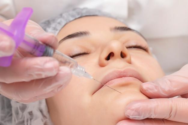 Primer del cosmetólogo que inyecta en la barbilla. ella sostiene una jeringa. cosméticos inyectados cara de mujer