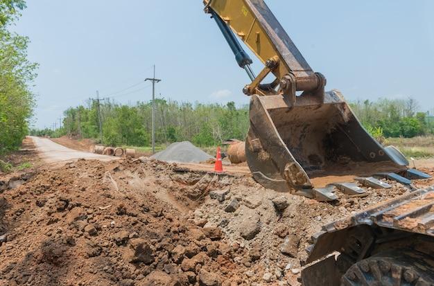 Primer del cubo del excavador cerca del sitio. excavador amarillo grande en campo de tierra en el día de verano.