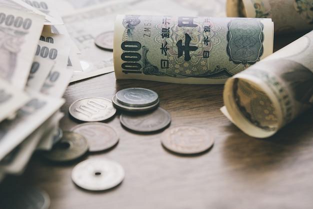 Primer de las cuentas y de las monedas de dinero de los yenes japoneses en el fondo de madera de la tabla