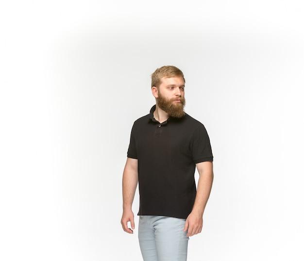 Primer del cuerpo del hombre joven en la camiseta negra vacía aislada en el fondo blanco.