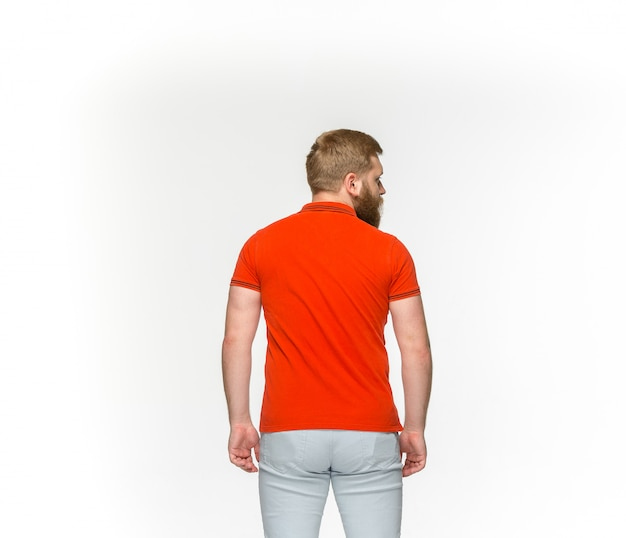 Primer del cuerpo del hombre joven en la camiseta roja vacía aislada en el fondo blanco. simulacros de concepto de diseño