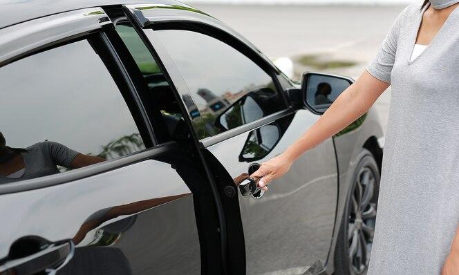 Primer de la mano de la mujer que abre una puerta de coche.