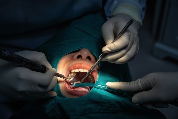 Primer dentista y asistente de operaciones de revisión y limpieza dental en clínica dental