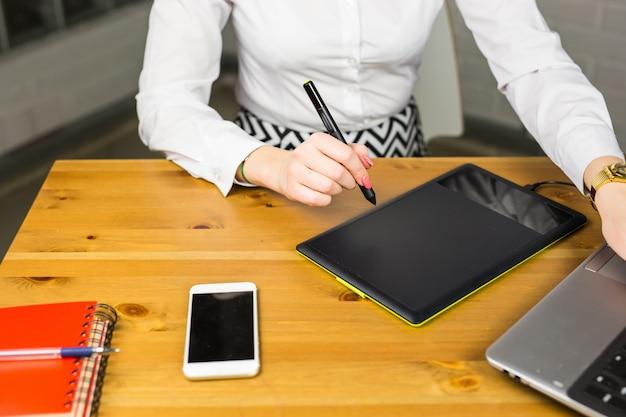 Primer del diseñador de sexo femenino en la oficina que trabaja con la tableta gráfica digital y la computadora portátil. retocador de fotografía sentado en el escritorio.