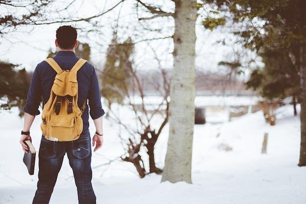 Primer disparo desde atrás de un hombre con una mochila amarilla y sosteniendo la biblia