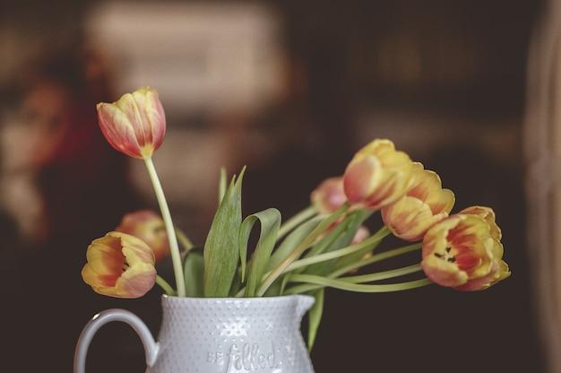 Primer disparo de enfoque selectivo de tulipanes amarillos y rojos en un jarrón de cerámica blanca