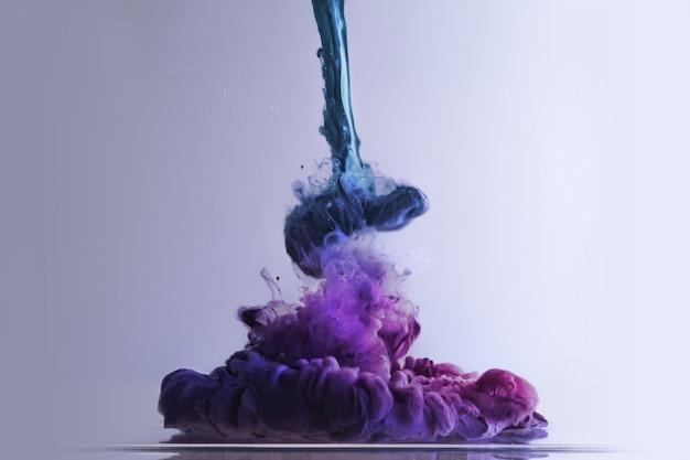 Primer disparo de explosión de tinta colorida sobre una superficie blanca