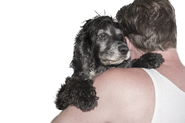 Primer disparo de un hombre abrazando a un perro negro detrás en blanco