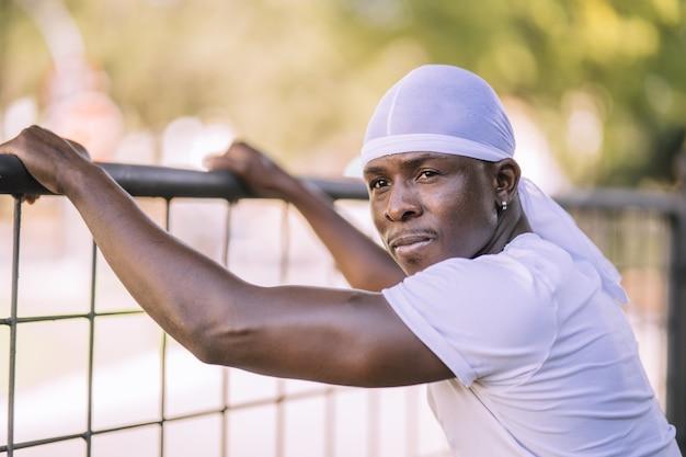 Primer disparo de un hombre afroamericano con una camisa blanca posando en el parque