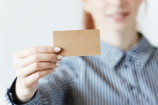 Primer disparo de manos femeninas sosteniendo una tarjeta de visita en blanco