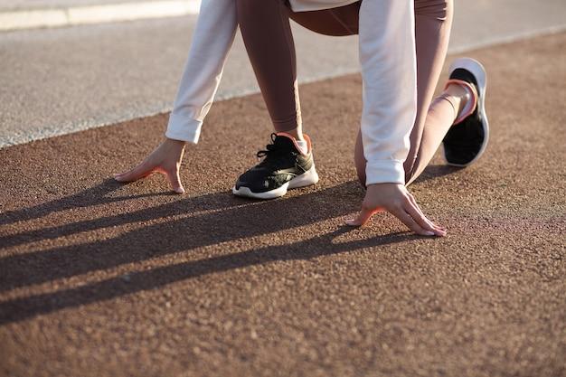El primer disparo de una mujer deportiva en la posición inicial está listo para correr. espacio para texto