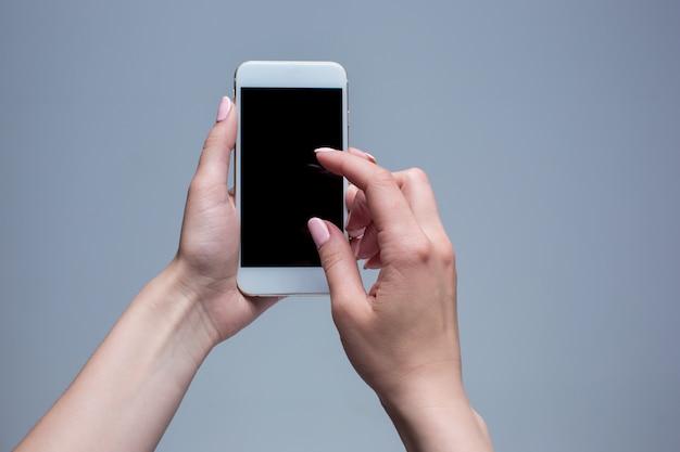 Primer disparo de una mujer escribiendo en el teléfono móvil sobre fondo gris. manos femeninas sosteniendo un teléfono inteligente moderno y apuntando con el dedo.