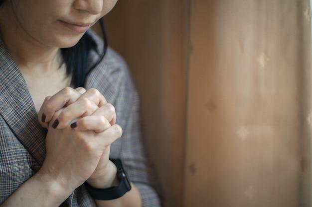 Primer disparo de una mujer rezando en casa. concepto cristiano.