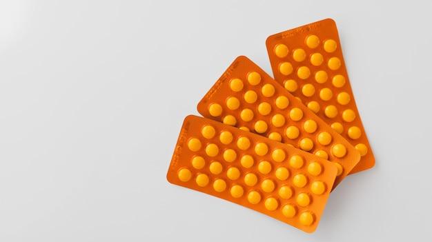 Primer disparo de pastillas de color naranja sobre fondo blanco.