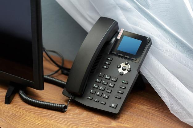 Primer disparo de un receptor de teléfono con botones y textos en él en una habitación de hotel.
