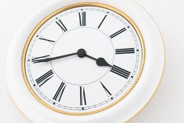 Primer disparo de un reloj de pared con números romanos blancos