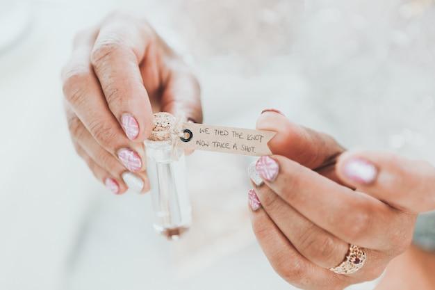 Primer disparo selectivo de una mujer sosteniendo una pequeña botella de vidrio con palabras escritas en una etiqueta