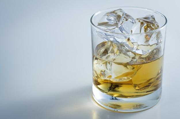 Primer disparo de un vaso lleno de hielo y un poco de whisky aislado sobre un fondo blanco.