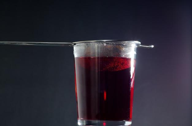 Primer disparo de un vaso de té rojo en la oscuridad