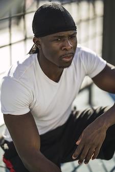 Primer disparo vertical de un hombre afroamericano con una camisa blanca sentado en un piso de concreto