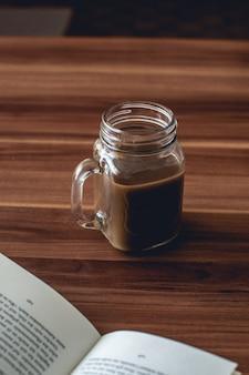 Primer disparo vertical de una taza de cristal de chocolate caliente en una mesa de madera