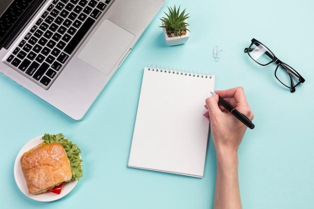 Primer de la escritura de la empresaria en la libreta espiral con la pluma en el escritorio de oficina