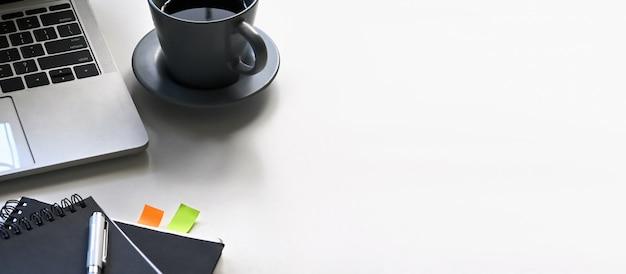 Primer espacio de copia portátil, taza de café, cuaderno, libro de calendario y pluma que se juntan en el escritorio de trabajo blanco. tamaño de panorama de banner de escritorio de oficina moderna.
