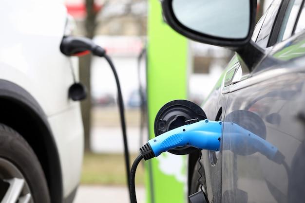 Primer de la estación de carga pública del coche eléctrico en la calle de la ciudad. fuente de alimentación para electrocar. reabastecimiento de combustible para la movilidad eléctrica. innovación y concepto de vehículo moderno.