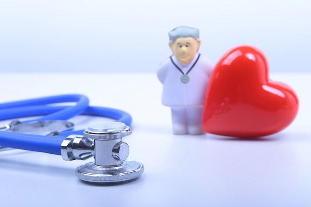 Primer del estetoscopio en el fondo del doctor y corazón rojo.