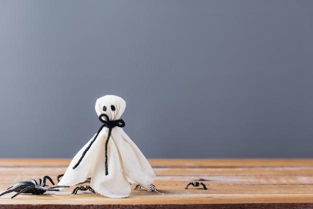 Primer fantasma blanco y araña en la pared de madera gris