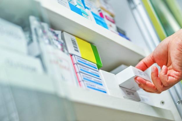 Primer farmacéutico mano sujetando la caja de la medicina en farmacia